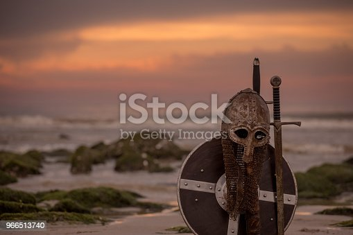 istock Medieval warrior equipment on a cold seashore at dusk 966513740