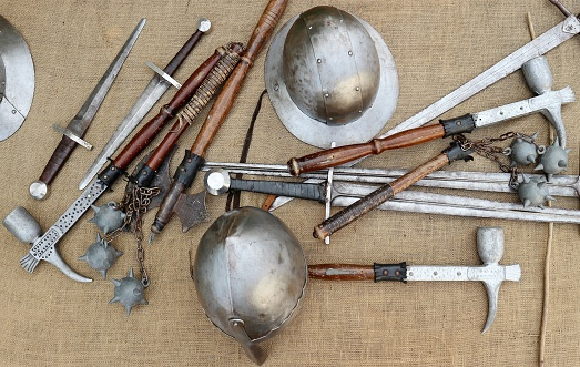 Medieval weapons and helmets on jute canvas. Top view.