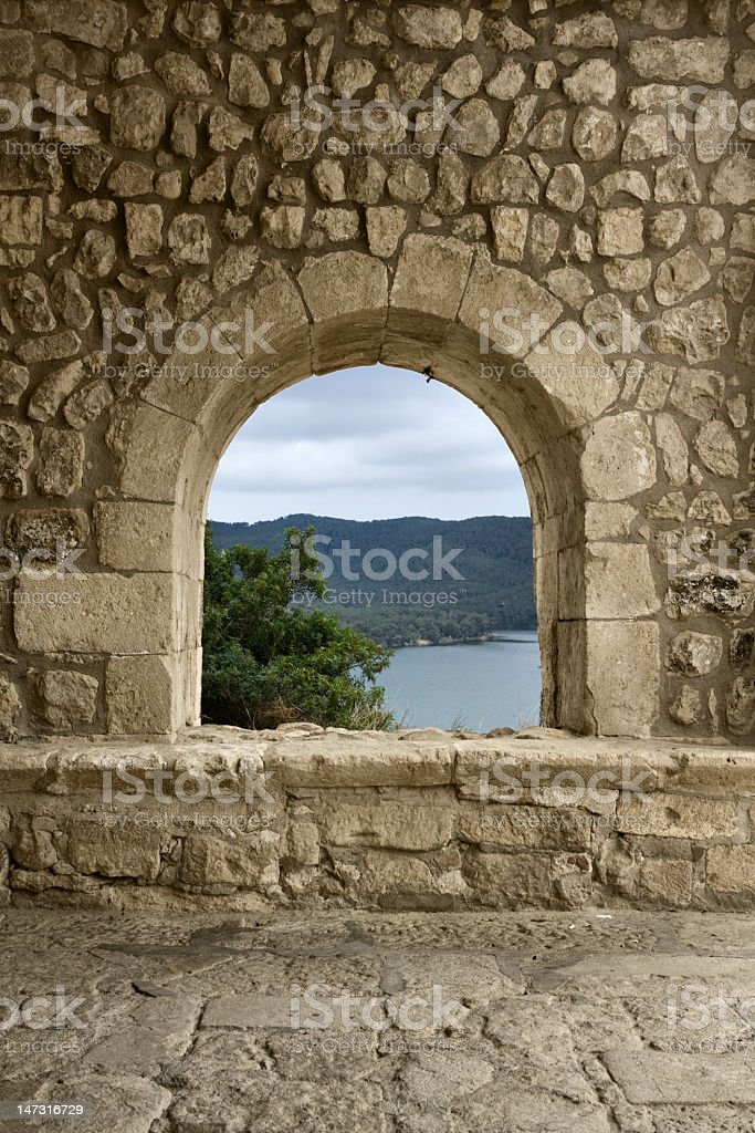 A medieval window made of solid rocks stock photo