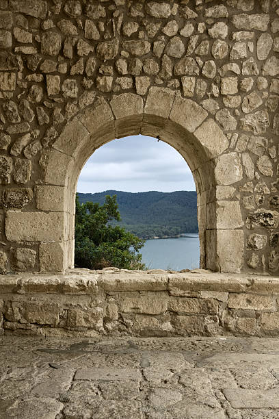 A medieval window made of solid rocks A window/arch at the entrance of a romanesque church in a spanish village (Castellet, Barcelona). A beautiful landscape may be seen through it. romanesque stock pictures, royalty-free photos & images