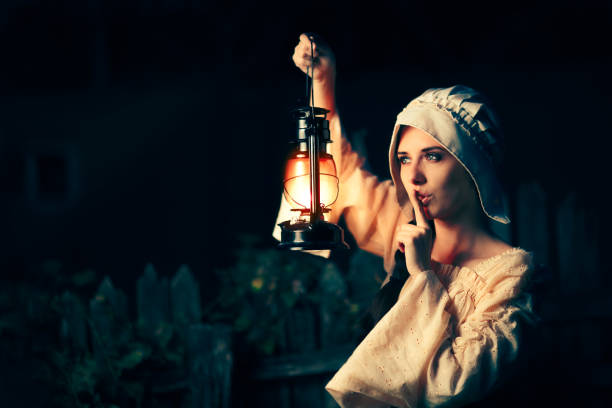 Medieval Woman with the Finger on the Lips Holding a Lamp stock photo