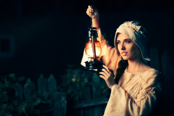 Medieval Woman with Vintage Lantern Outside at Night Cosplay girl in Halloween costume holding a lamp bonnet stock pictures, royalty-free photos & images