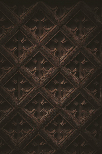 Dark, low key wooden shapes and pattern from the exterior of a 16th century church door.