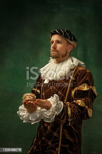 Fast food joyful. Portrait of medieval young man in vintage clothing with wooden frame on dark background. Male model as a duke, prince, royal person. Concept of comparison of eras, modern, fashion.