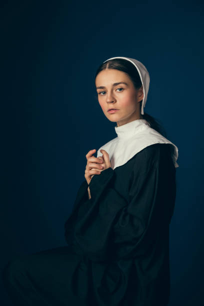 Medieval young woman as a nun Hope and faith. Medieval young woman as a nun in vintage clothing and white mutch sitting on the chair on dark blue background. Concept of comparison of eras. Vintage portrait. bonnet stock pictures, royalty-free photos & images