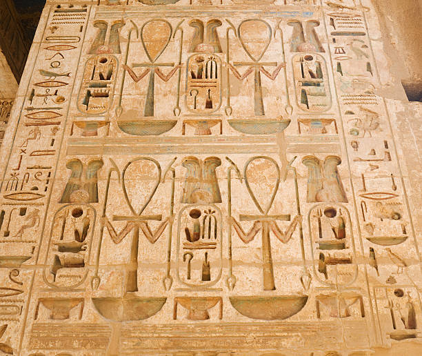 Medinet Habu Temple Stone carving with ancient Egyptiam symbols and hieroglyphics.  Tomb Of Ramses III stock pictures, royalty-free photos & images