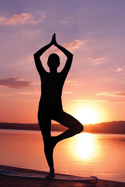Meditating at sunrise stock photo