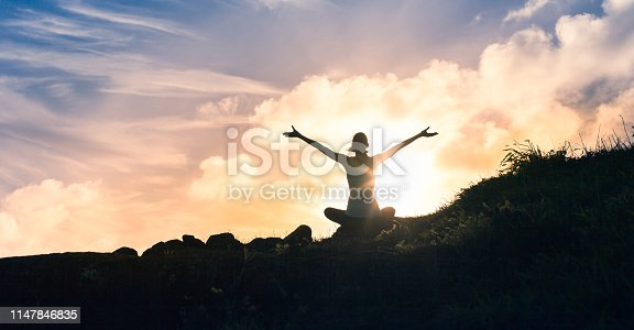 Woman meditating at sunset. Location Hawaii, USA.