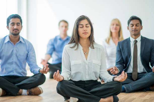 Meditating at the Office A multi-ethnic group of young business men and women in semi-casual office clothes are sitting on the floor and meditating to relax in an indoor, sunlit office. mental wellbeing stock pictures, royalty-free photos & images