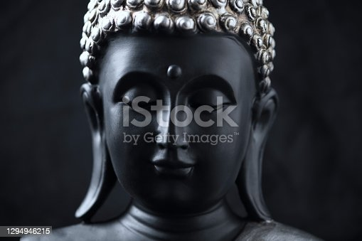 istock Meditating Buddha Statue isolated on black background. 1294946215