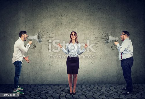 istock meditating business woman paying no attention to angry men screaming at her in megaphone 982740318