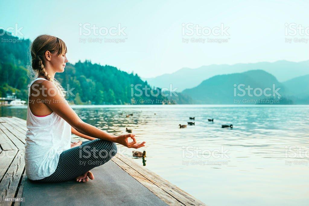Meditating by the lake stock photo