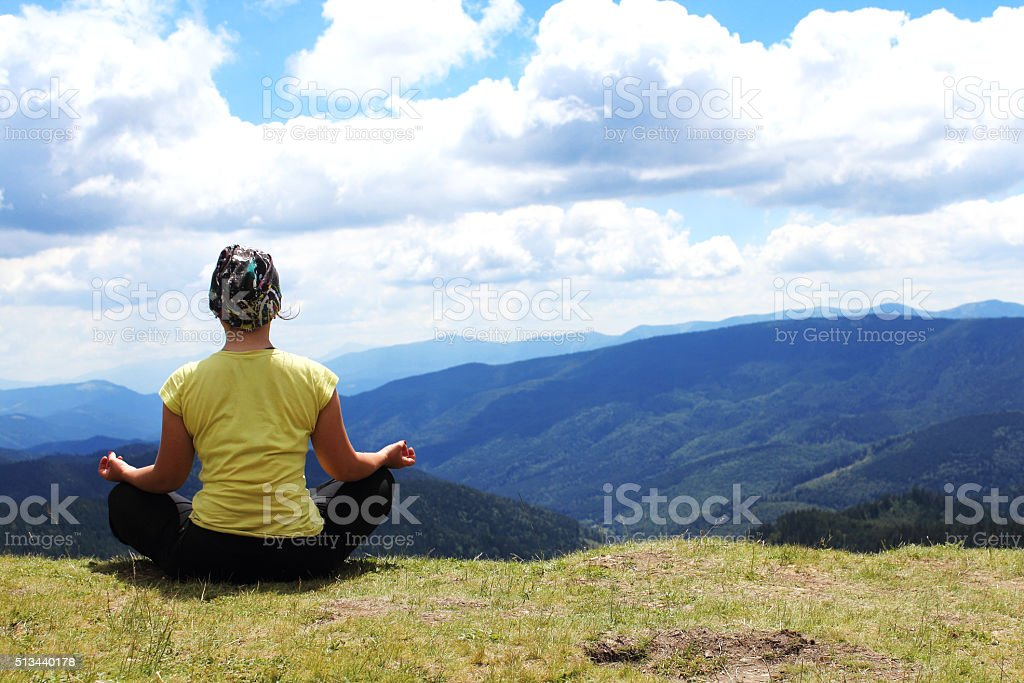 Meditating girl in mountains stock photo