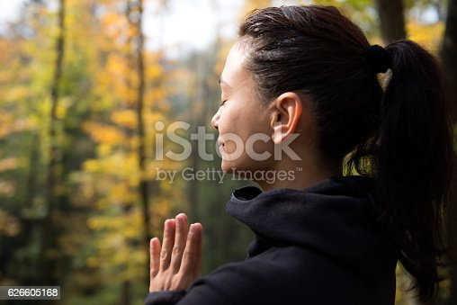 Female is meditating in forest with closed eyes.
