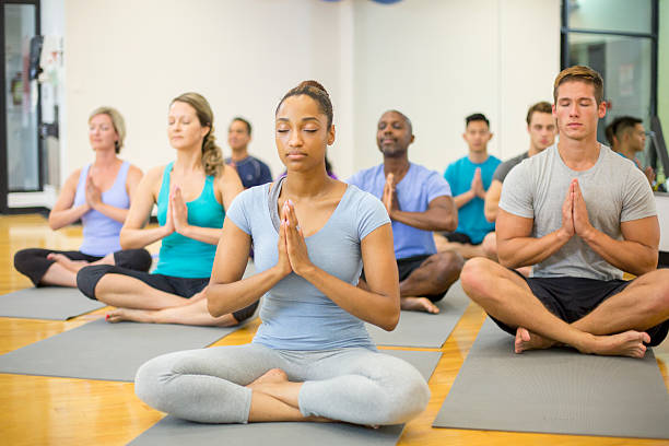 Meditating in Prayer Pose A multi-ethnic group of adults are taking a yoga class at the gym. They are meditating on their yoga mats. yoga class stock pictures, royalty-free photos & images