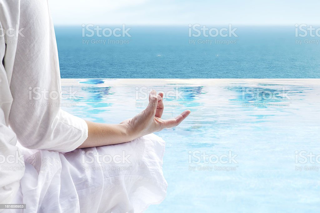 Meditating in the infinity pool stock photo