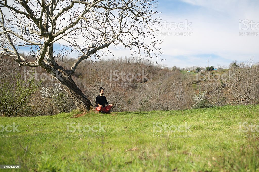 Meditating man having a divine moment in nature stock photo