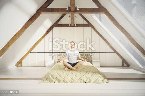 istock Meditating man in loft bedroom 611310760