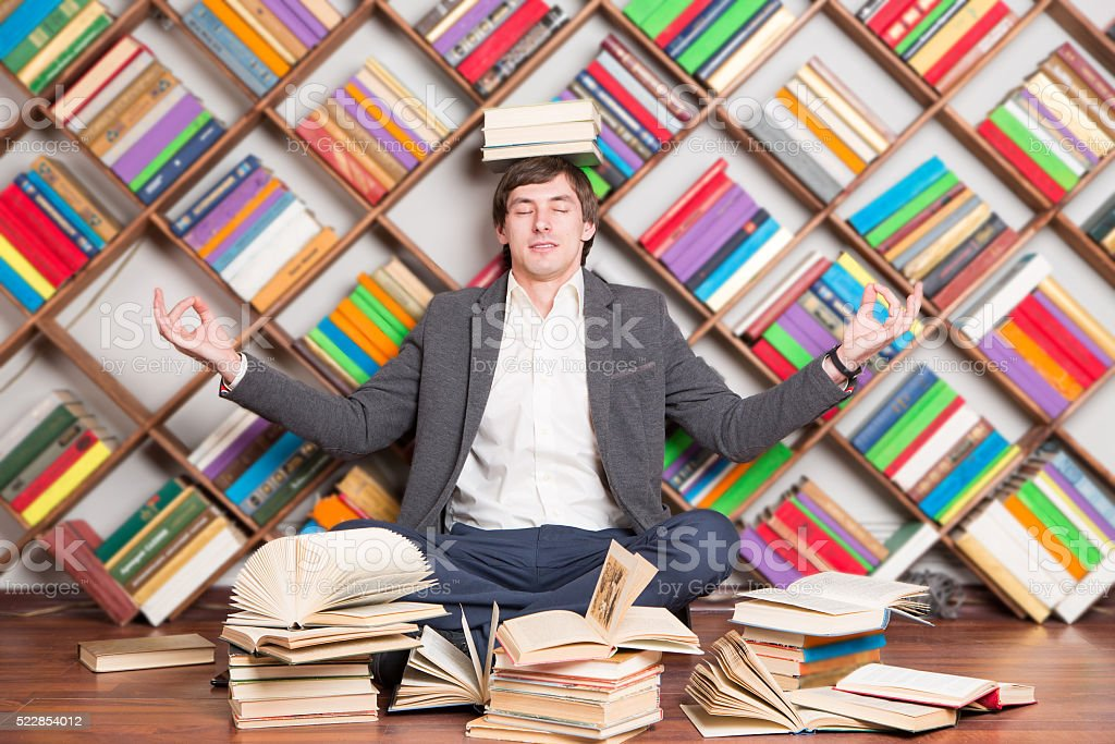meditating man in the library with books on head stock photo