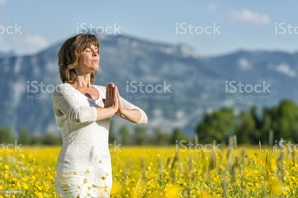 meditating mature woman standing in flower meadow stock photo