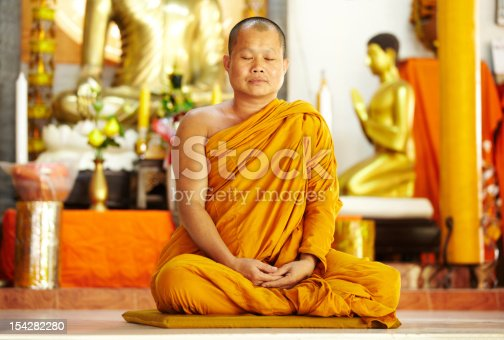A monk meditating in the lotus position in front of golden Buddhas