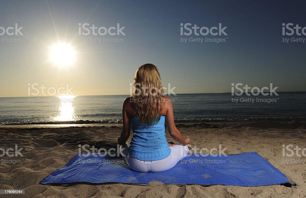 Meditating on beach with sunrise royalty-free stock photo