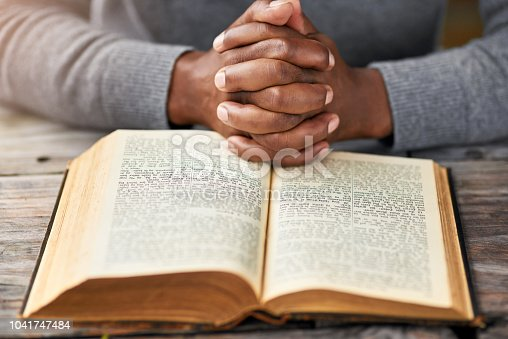 High angle shot of an unrecognizable man reading his bible while sitting outside