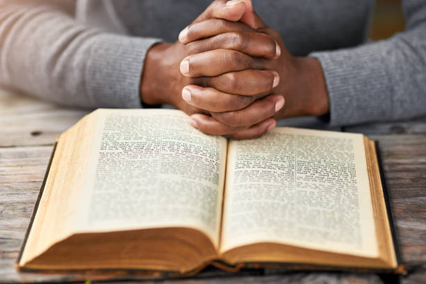 Meditating on God's word High angle shot of an unrecognizable man reading his bible while sitting outside christianity stock pictures, royalty-free photos & images