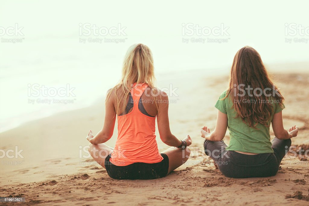 Meditating on the beach stock photo