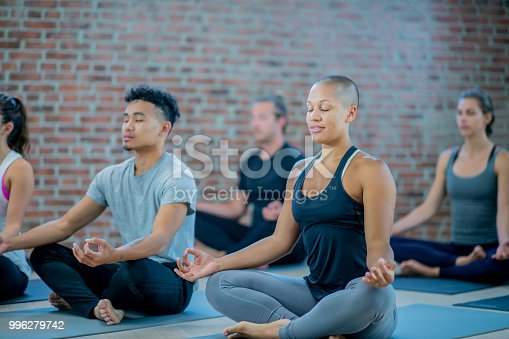 A multi-ethnic group of adults are indoors in a fitness center. They are meditating with their eyes closed while sitting on exercise mats.