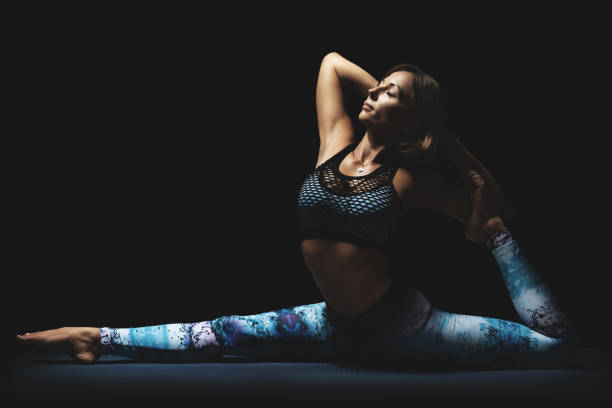 Meditation and yoga concept. Athletic young woman in split pose. Black background, charming light, serene mood. stock photo