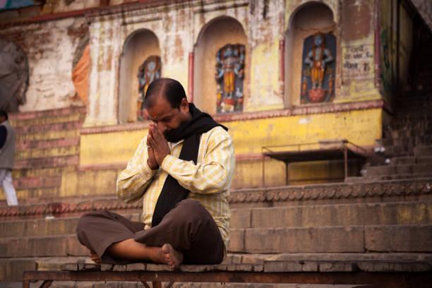 meditation at near ganga river, varanasi, india. - hinduism stock photos and pictures
