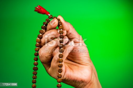 Meditation beads in hand on a deep green background with copy space