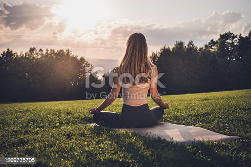Outdoors yoga at sunrise in public park.