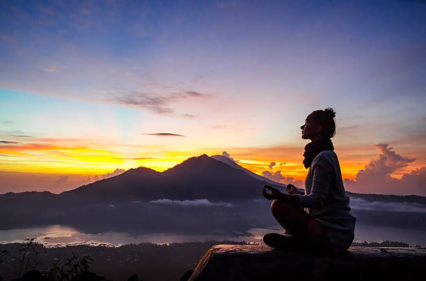 Meditation in the mountains Silhouette of a girl that does yoga and meditation in the mountains at dawn. Stock image. lotus position stock pictures, royalty-free photos & images