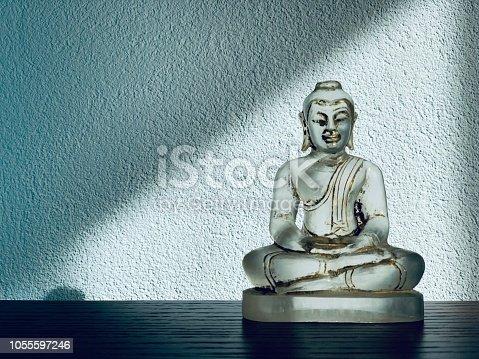 Meditation - little transparent glass buddha statue on blue background