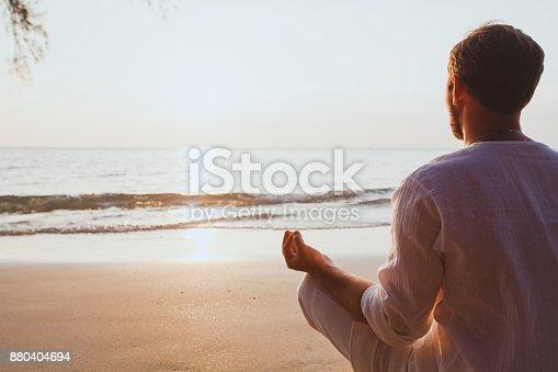 istock meditation, man practicing yoga at sunset beach 880404694