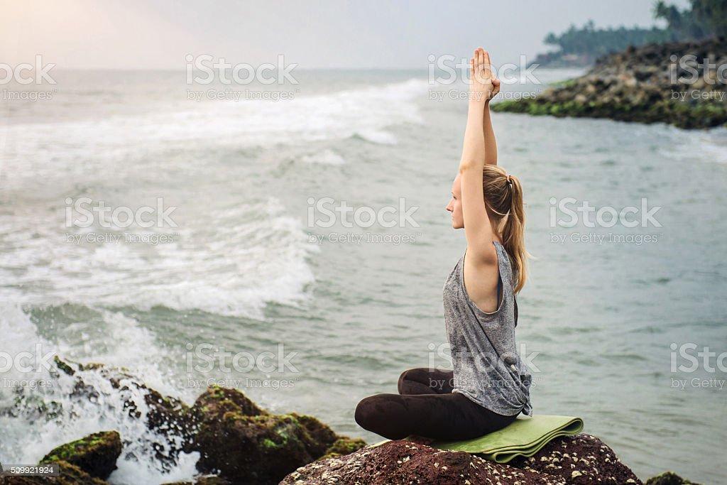 Meditation near the sea on sunset stock photo