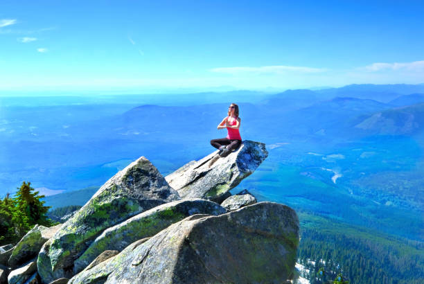 Meditation on rock with mountains and valley views. Mount Pilchuck. Seattle. Washington. United States. stock photo
