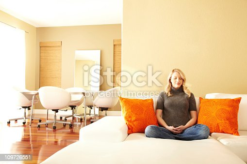 Woman meditating on a white sofa in modern design living room with orange pillows