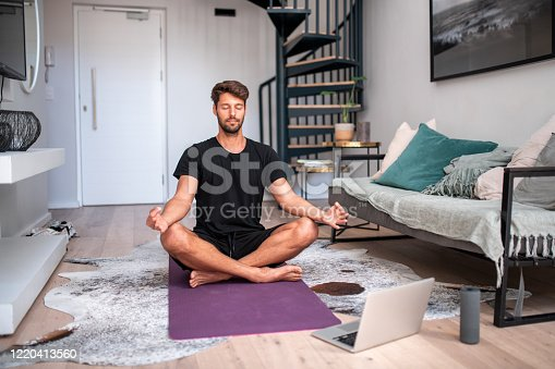 Handsome young man meditating in the living room