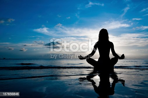 Silhouette of woman in lotus position sitting in sea and medditating