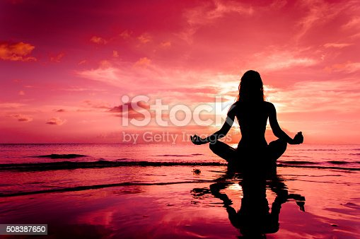 Silhouette of woman in lotus position sitting in water