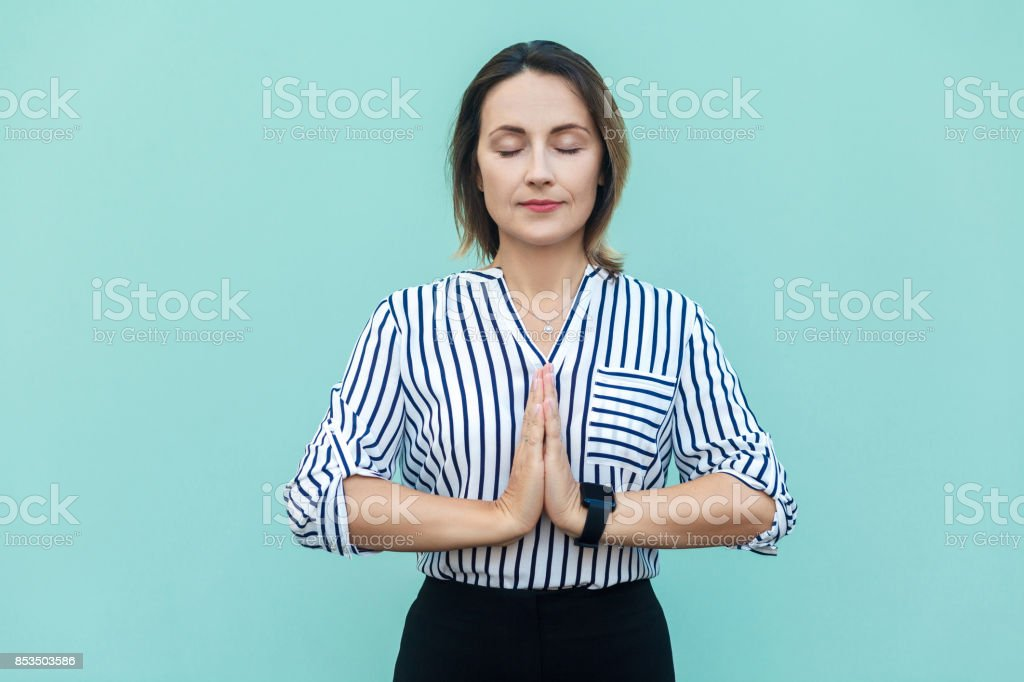 Meditation, Religion und spirituelle Praktiken. Schöne Geschäftsfrau beim Yoga im Haus am blauen Lichtwand, Augen geschlossen, halten, hält Finger in Mudra-Geste. – Foto