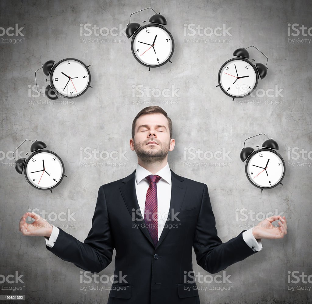 Meditative businessman is pondering about time management. stock photo