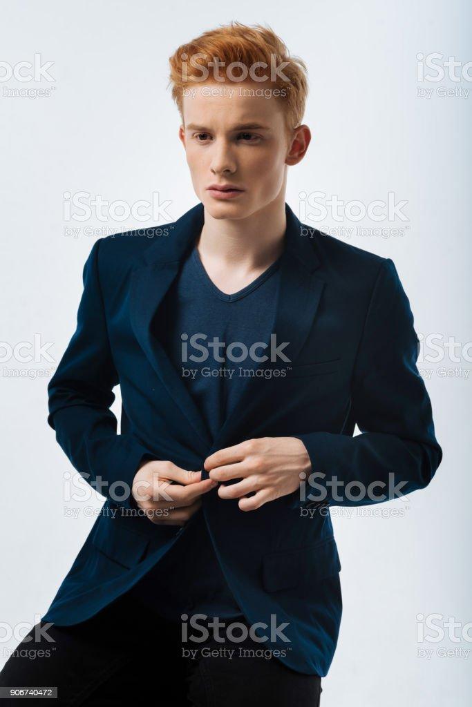 Meditative man buttoning his jacket up stock photo
