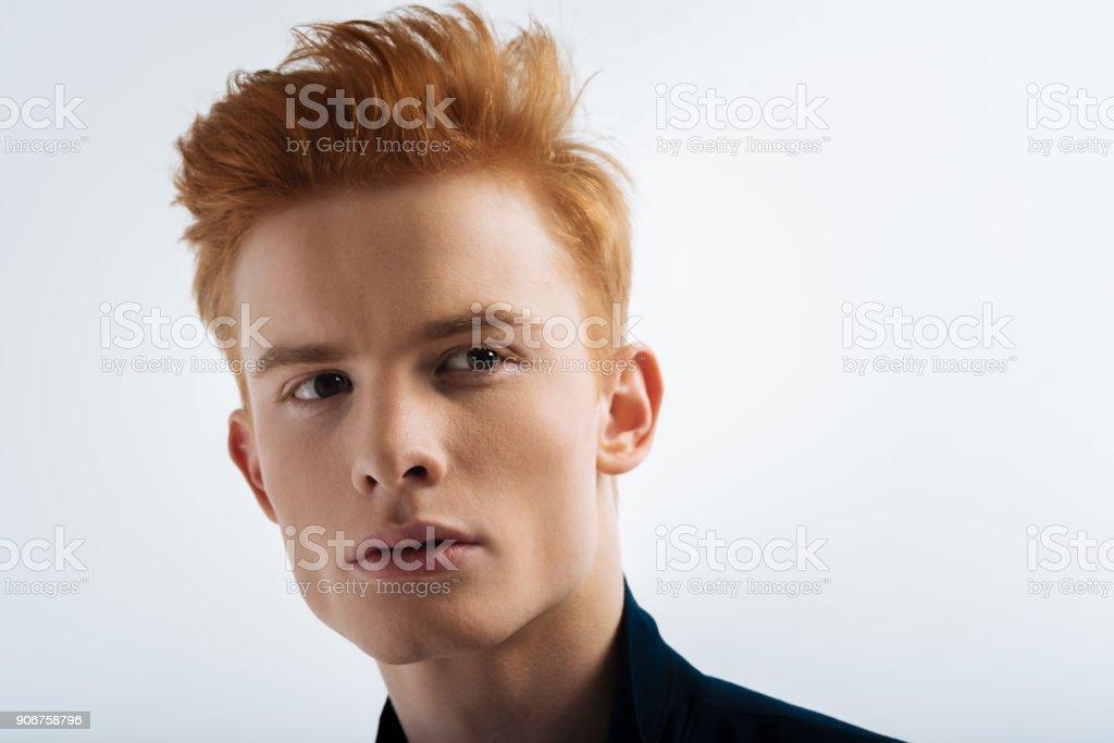 Meditative red-headed young man thinking stock photo