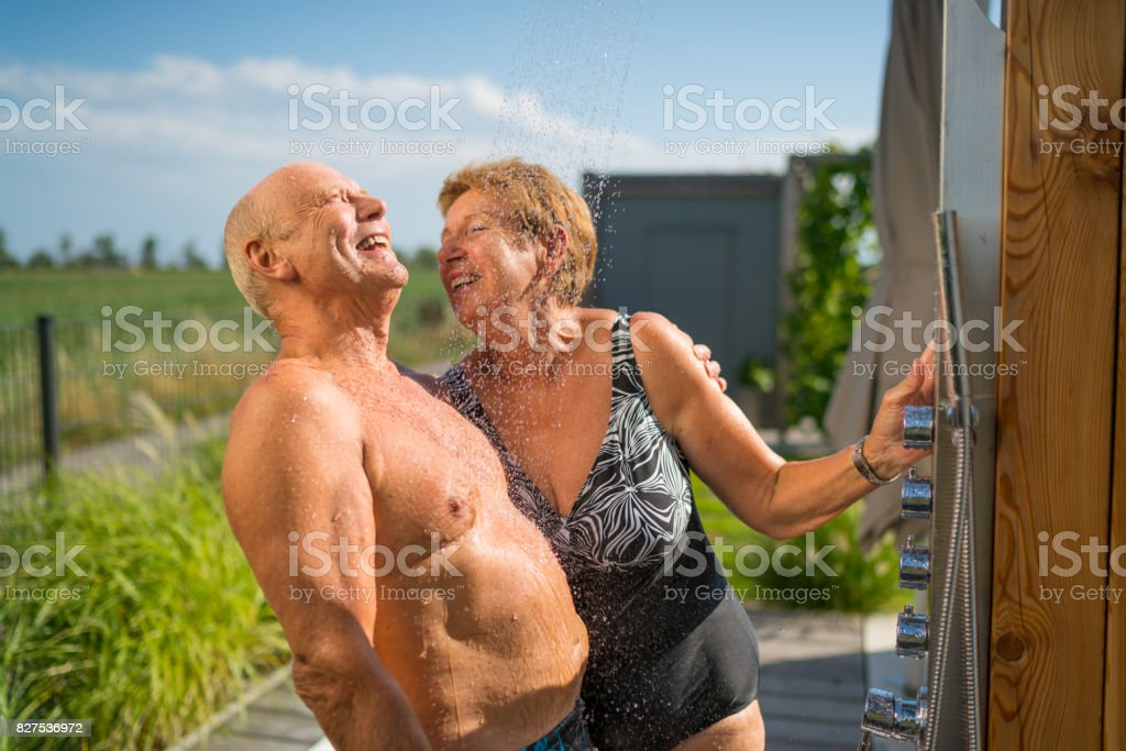 Mediterranean Active Seniors, enjoying garden shower in summer стоковое фото