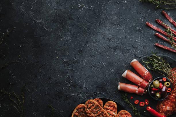 aperitivos mediterráneos. jamón, chorizo, fuet y pan crujiente sobre fondo oscuro con espacio de copia. - fuet sausages fotografías e imágenes de stock