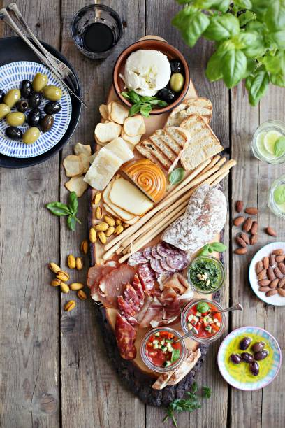 Mediterranean appetizers table concept. Diner table with antipasto selection: cured meat and salami, gazpacho soup, jamon, olives, cheese, hummus and vegetables. stock photo